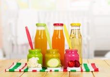 Krus och flaskor behandla som ett barn puréfruktsaft som isoleras på vit bakgrund Royaltyfri Fotografi