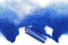 Kruset med spillda blått blänker magiska himmelska blått blänker spill ut ur en krus som isoleras på vit bakgrund royaltyfria foton