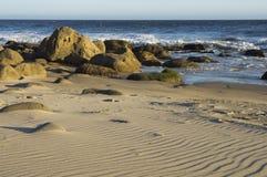 Krusningar i sand med vaggar och havet Arkivbilder