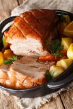 Krustenbraten Pork Roast with Crispy Rind with vegetables close-up in a frying pan. Vertical. Krustenbraten Pork Roast with Crispy Rind with vegetables close-up royalty free stock image
