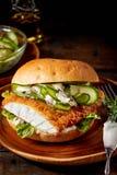 Kruszący rybi hamburger z ogórkiem obraz royalty free