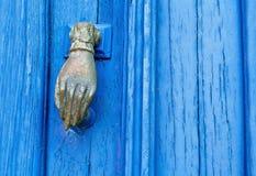 Kruszcowa drzwiowego knocker ręka - stary błękitny drewniany drzwi Obraz Stock