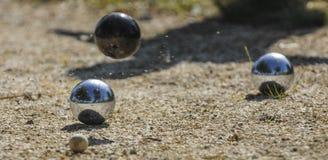 Kruszcowe petanque trzy piłki i mała drewniana dźwigarka fotografia royalty free