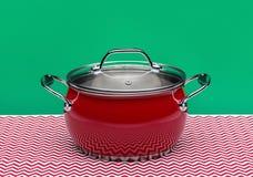 Kruszcowy czerwony kucharstwo garnek z szklanym deklem odizolowywającym na białym tle fotografia stock