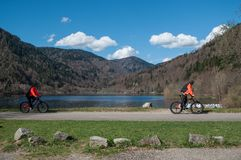 Panorama of lake of Kruth with beautiful cloudy sky and mountain bike couple. Kruth - France - 12 April 2018 - panorama of lake of Kruth with beautiful cloudy Royalty Free Stock Photography