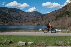 Panorama of lake of Kruth with beautiful cloudy sky and mountain bike couple. Kruth - France - 12 April 2018 - panorama of lake of Kruth with beautiful cloudy Stock Images