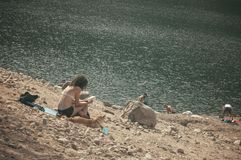 Woman in swimsuit reading in border lake royalty free stock photos