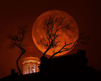 Krwawoczerwony Supermoon z kościół i drzewem w złej pogodzie Obrazy Stock