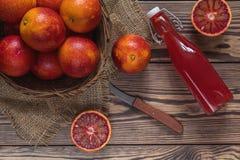 Krwionośnej pomarańcze owoc w łozinowego kosza i butelki soku na zmroku w zdjęcie royalty free