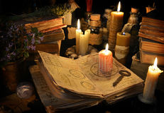 Krwista świeczka na czarownicy książce w świeczki świetle fotografia stock