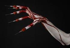Krwista ręka z strzykawką na palcach, palec u nogi strzykawki, ręka opryskuje, okropna krwista ręka, Halloween temat, żywy trup l Zdjęcia Royalty Free