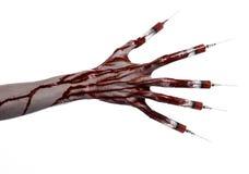 Krwista ręka z strzykawką na palcach, palec u nogi strzykawki, ręka opryskuje, okropna krwista ręka, Halloween temat, żywy trup l Fotografia Stock
