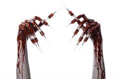 Krwista ręka z strzykawką na palcach, palec u nogi strzykawki, ręka opryskuje, okropna krwista ręka, Halloween temat, żywy trup l Zdjęcie Royalty Free