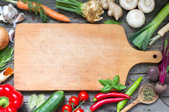 Krydda örter och grönsakmatbakgrund och den tomma skärbrädan royaltyfria foton