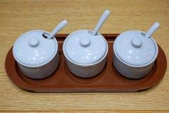 Krydda behållareuppsättningen för att nudel ska bestå av kajennpeppar, socker och vinäger på trätabellen arkivbild
