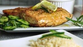 Krydda och laga mat laxfisken med ris och gurkan stock video
