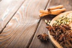 Krydda på ett texturerat träbakgrundsnärbild- och kopieringsutrymme Kanel stjärnaanis, fänkål, kryddnejlikor som kryddar temasala arkivfoto