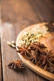 Krydda på ett texturerat träbakgrundsnärbild- och kopieringsutrymme Kanel stjärnaanis, fänkål, kryddnejlikor som kryddar temasala arkivbild