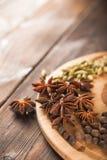 Krydda på ett texturerat träbakgrundsnärbild- och kopieringsutrymme Kanel stjärnaanis, fänkål, kryddnejlikor som kryddar temasala royaltyfri foto