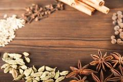 Krydda på ett texturerat träbakgrundsnärbild- och kopieringsutrymme Kanel stjärnaanis, fänkål, kryddnejlikor som kryddar temasala royaltyfria bilder