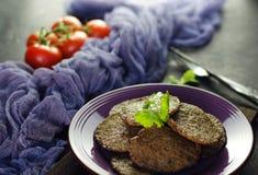 Kryddade pannkakor för feg lever med grönsaker Hem- pannkakor för stekt kycklinglever på mörkt bräde För sidomaträtt för feg leve royaltyfria bilder