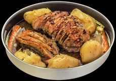 Kryddade snittgrisköttHam Chunks Stuffed With Bacon Oven Baked With Whole Red potatisar i naturlig sky på svart bakgrund arkivfoto
