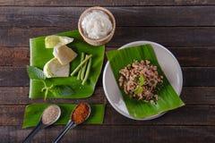 Kryddig finhackad grisköttsallad på det nya bananbladet Arkivbild