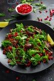Kryddig frasig andsallad med granatäpplefrö, limefrukt och lös grön rucola fotografering för bildbyråer