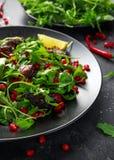 Kryddig frasig andsallad med granatäpplefrö, limefrukt och lös grön rucola royaltyfri bild