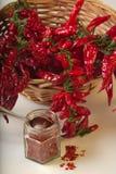 Kryddig jordning för röd peppar i den glass kruset, med sunda torkade peppar i korgen Royaltyfria Foton