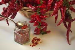 Kryddig jordning för röd peppar i den glass kruset, med sunda torkade peppar i korgen Arkivfoton
