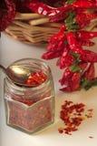 Kryddig jordning för röd peppar i den glass kruset, med sunda torkade peppar i korgen Arkivfoto