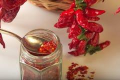 Kryddig jordning för röd peppar i den glass kruset, med sunda torkade peppar i korgen Royaltyfri Foto