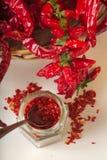 Kryddig jordning för röd peppar i den glass kruset, med sunda torkade peppar i korgen Arkivbild