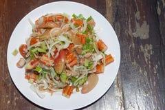 Kryddig lax- och krabbapinne eller kanikamasallad med grönsaken i den vita plattan på trätabellen fotografering för bildbyråer