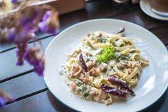 Kryddig spagetti med bacon och ost på en trätabell i en restaurang Royaltyfria Foton
