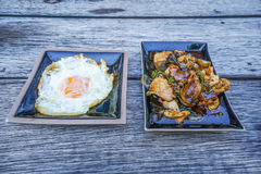 Kryddig stekt kyckling med basilikamaträtten och stekt ägg på tabellen Arkivbilder