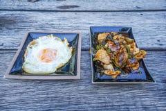 Kryddig stekt kyckling med basilikamaträtten och stekt ägg på tabellen Fotografering för Bildbyråer