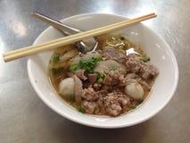 Kryddig thai äggnudel med griskött och fishball Arkivbild