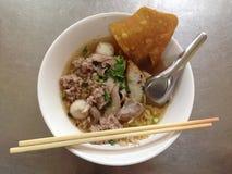 Kryddig thai äggnudel med griskött och fishball Arkivbilder