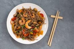 Kryddiga bovetenudlar med skaldjur och grönsaker, bästa sikt arkivbilder