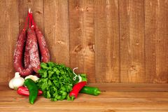 Kryddiga Chorizosalamikorvar som hänger på en lantlig träbakgrund royaltyfri foto