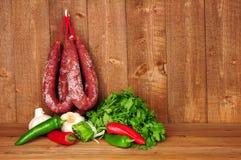 Kryddiga Chorizosalamikorvar som hänger på en lantlig träbakgrund royaltyfri fotografi