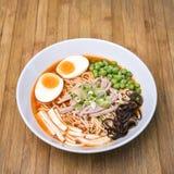 Kryddiga Tom Yum, krämiga grisköttRamen med ägget, Sugar Pea, Tofu och M Arkivfoto