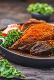 Kryddigt bakat nötkött med grönkålsallad i svart platta på mörk backgrou arkivbild