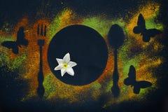 Kryddigt kort som göras av varma kryddor, skedar, gafflar, fjärilar och pingstliljablommor i gurkmeja, paprika och chili på en ko arkivbilder