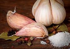 Kryddnejlika av vitlök och kryddahögen av salt arkivfoto