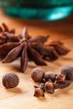 Kryddnejlikor kryddpeppar, stjärnaanis på en träbrädecloseup Arkivfoto