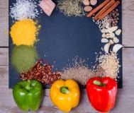 Kryddor, örter och ny peppar kritiserar på magasinet på en gammal lantlig tabell Röda, gula och gröna nya peppar Top beskådar Fotografering för Bildbyråer