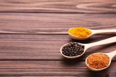 Kryddor blandar i sked på en brun träbakgrund Top beskådar royaltyfri foto